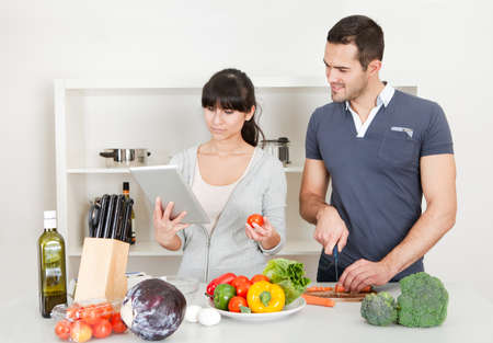 Lovely young couple cooking in the kitchen at home photo