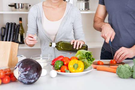 aceite de cocina: Cocina hermosa joven pareja en la cocina en casa. A�adir el aceite de oliva