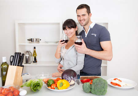 Lovely young couple cooking in the kitchen and drinking wine photo