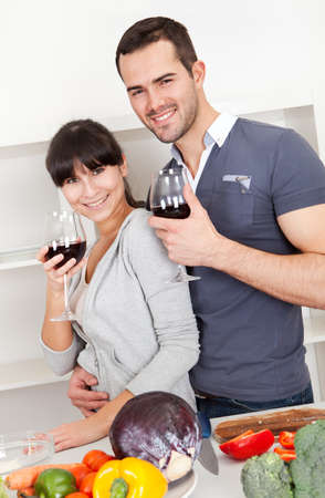 Lovely young couple cooking in the kitchen and drinking wine Stock Photo - 13019874