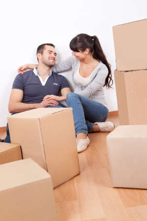family moving house: Happy young couple moving into new house Stock Photo
