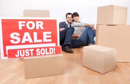 cardboard house: Happy young couple moving into new house Stock Photo
