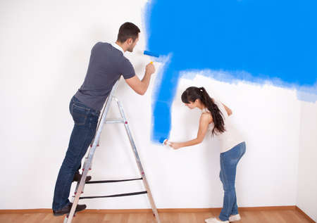 Young couple painting wall at home in blue Zdjęcie Seryjne