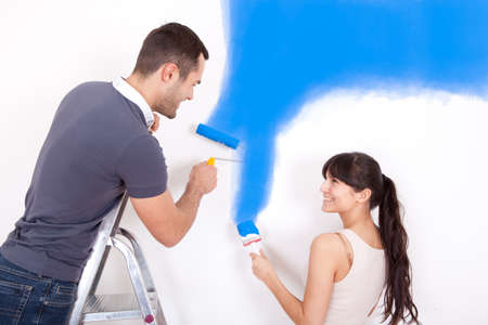painting and decorating: Young couple painting wall at home in blue Stock Photo