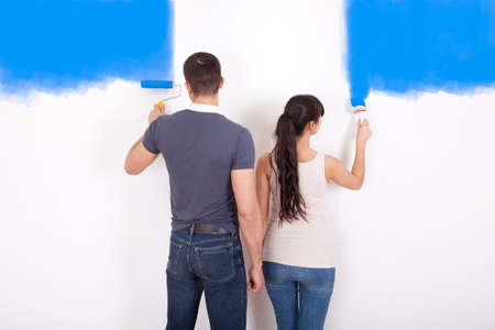 Young couple painting wall at home in blue photo