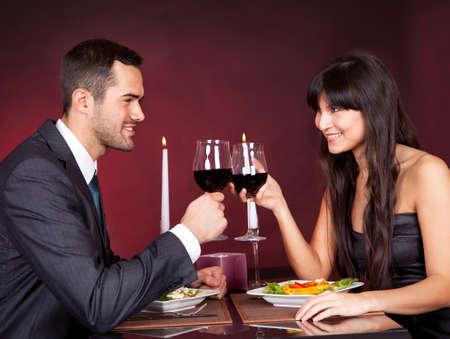Pareja joven encantador que tiene una cena romántica en el restaurante