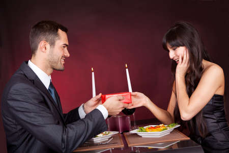 Man giving present to a woman at romantic dinner in restaurant photo
