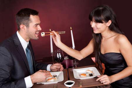 gourmet dinner: Encantadora pareja joven comer sushi en el restaurante Foto de archivo