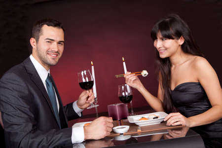 Lovely young couple eating sushi in restaurant photo
