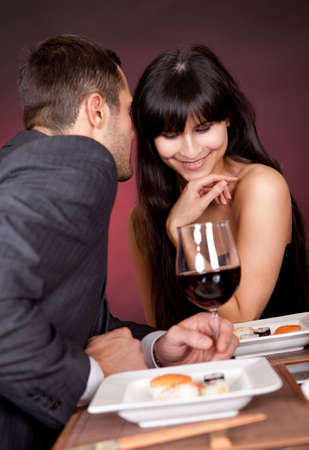 complement: Young couple having romantic conversation at restaurant