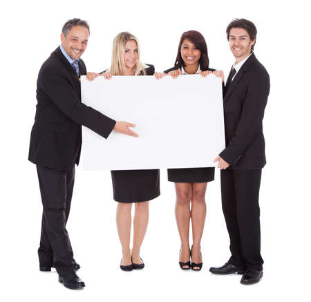 woman holding sign: Group of happy business colleagues holding billboard isolated on white background