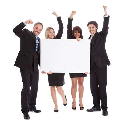 holding a sign: Group of happy business colleagues holding billboard isolated on white background