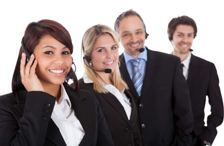 call centre girl: Confident business team with headset standing in a line against white background Stock Photo