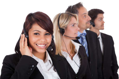 Confident business team with headset standing in a line against white background photo