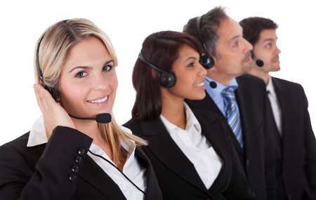 sales executive: Confident business team with headset standing in a line against white background Stock Photo