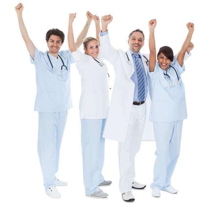 Group of doctors celebrating success. Isolated on white photo