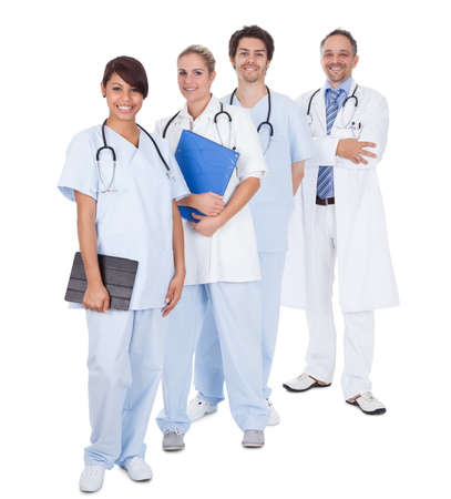standing in line: Group of doctors standing together isolated over white background