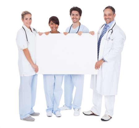leeg bord: Groep artsen presenteren leeg bord. Geà ¯ soleerd op wit Stockfoto
