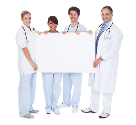 Group of doctors presenting empty board. Isolated on white photo