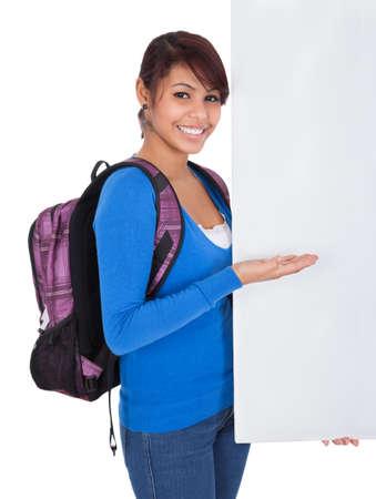 mochila escolar: Hermosa chica estudiante de la presentación de bandera de vacío. Aislado en blanco Foto de archivo