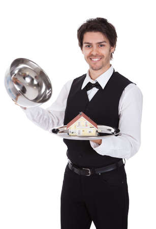 Portrait of a butler with model of a house on tray. Isolated on white photo