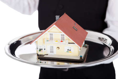 Close-up  of a butler with model of a house on tray. Isolated on white photo
