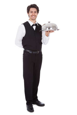 Portrait of a butler with bow tie and tray. Isolated on white photo