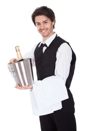 Portrait of a butler with bottle of champagne in a bucket. Isolated on white photo