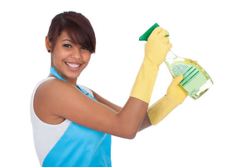 Cheerful young lady spraying cleaner liquid. Isolated on white photo