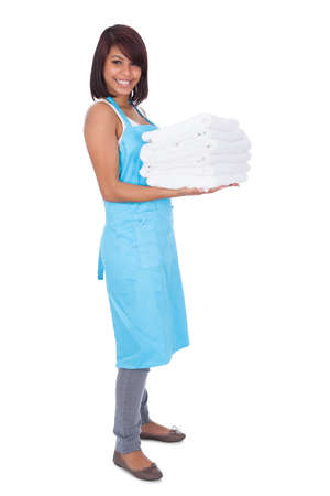 Smiling maid woman with towels. Isolated on white photo