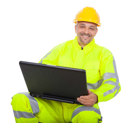 Portrait of worker in safety jacket working on laptop. Isolated on white photo