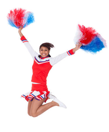 Smiling beautiful cheerleader with pompoms. Isolated on white photo