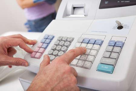 maquina registradora: Persona de las ventas al introducir el importe en la caja registradora en la tienda al por menor Foto de archivo