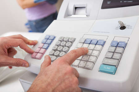 register: Sales person entering amount on cash register in retail store