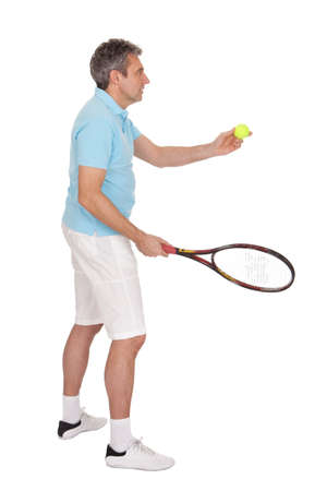 Mature man playing tennis. Isolated on white photo