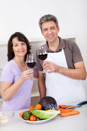 Senior couple cooking at home and drinking wine. Isolated on white photo
