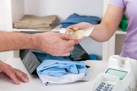 Close-up on paying for t-shirt in cash at store photo