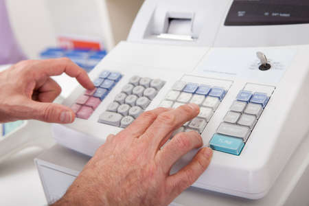 sales person: Sales person entering amount on cash register in retail store