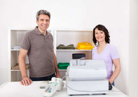 retailer: Portrait of cheerful sales persons in the retail store Stock Photo