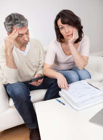 Unhappy mature couple in financial trouble at home photo
