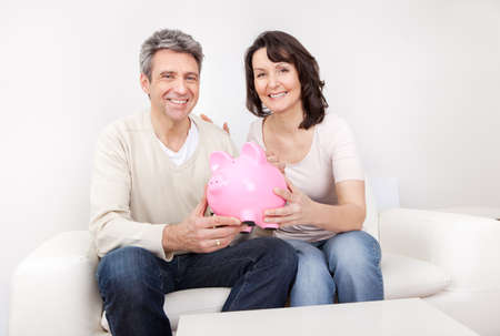 Mature couple saving money in piggybank at home Stock Photo - 13908045