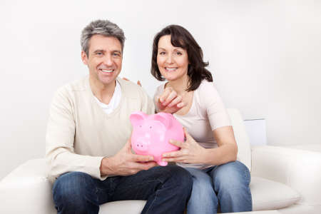 Mature couple saving money in piggybank at home photo