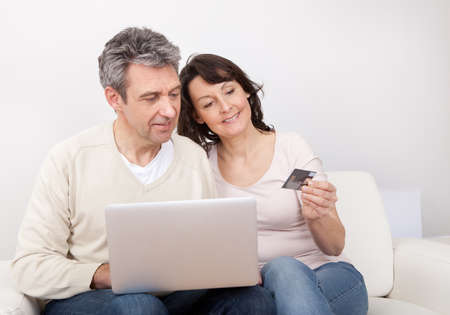 Mature couple shopping in internet using laptop at home photo