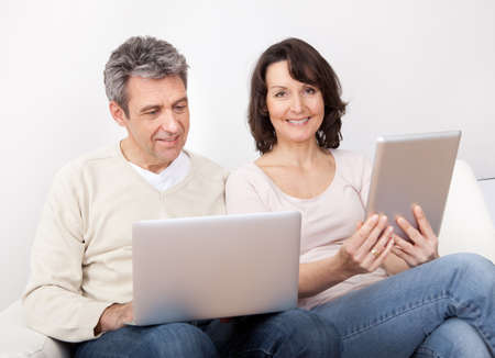 Mature couple using laptop and tablet in couch at home photo