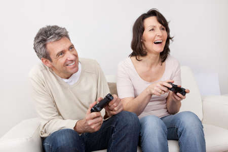 Mature couple playing videogames at home in the couch Stock Photo - 13907998