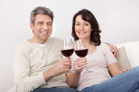 donne mature sexy: Coppia bere vino rosso a casa coppia Archivio Fotografico