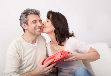 kiss couple: Mature man giving a present to his woman at home Stock Photo