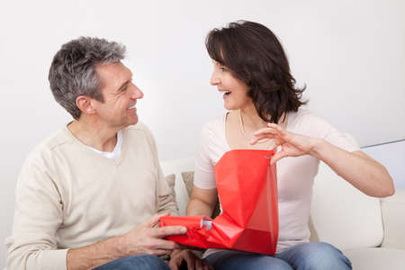 unwrapping: Mature man giving a present to his woman at home Stock Photo