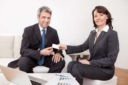 Two business people exchanging visiting card at the meeting photo