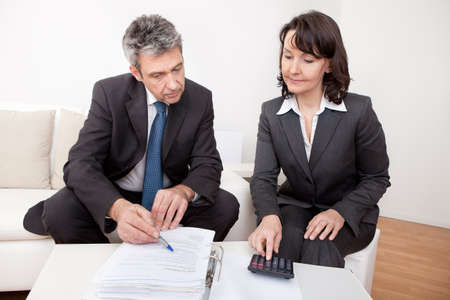 Two business people sitting in the couch discussing Stock Photo - 13908057